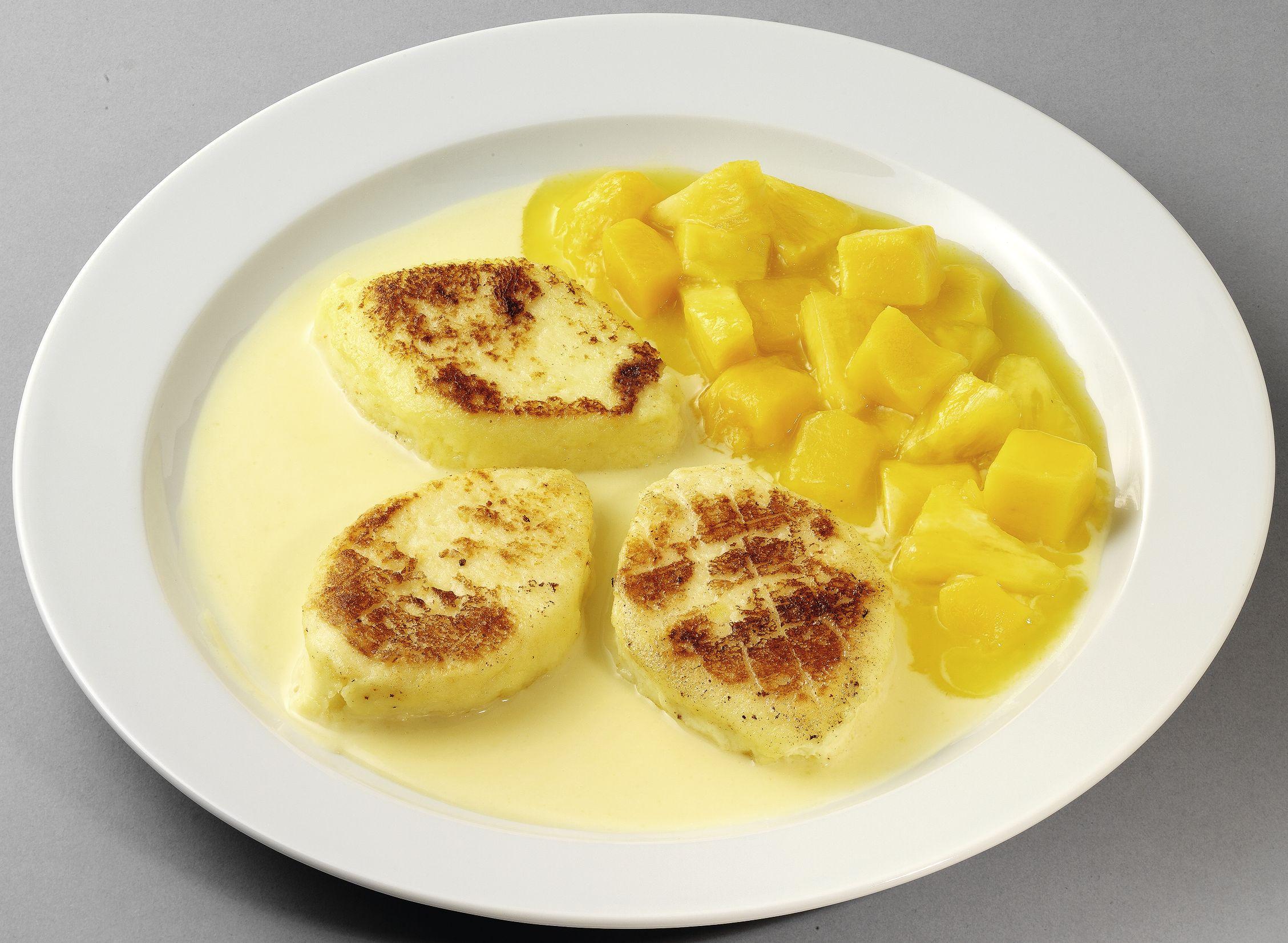 Süße Quarktaler auf aromatischer Vanillesoße mit Ananas-Mango-Kompott