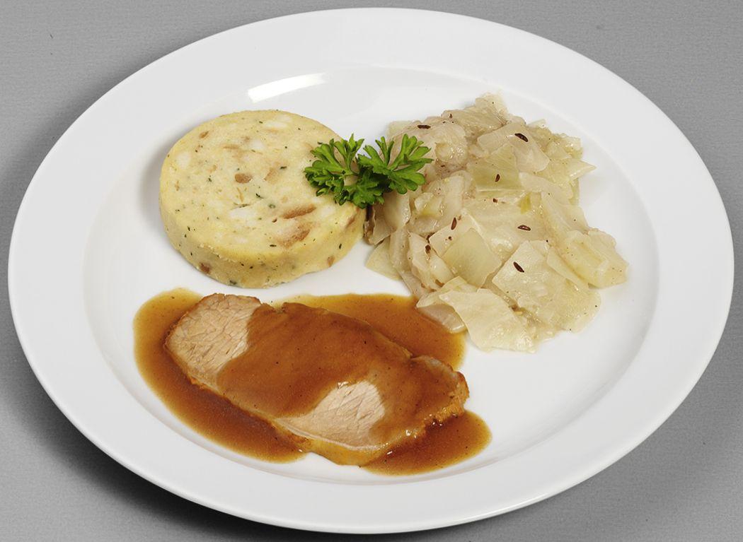 Klassischer Schweinebraten in Bratensoße mit bayrischem Weißkohl-Gemüse, dazu ein Serviettenknödel