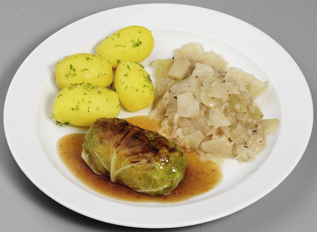 Hausgemachte Wirsingroulade vom Schwein und Rind in Bratensoße, dazu bayrisches Weißkohl-Gemüse und Petersilienkartoffeln